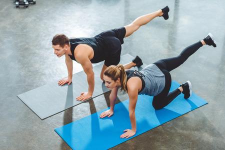 Foto de high angle view of sporty couple training on yoga mats in fitness studio - Imagen libre de derechos