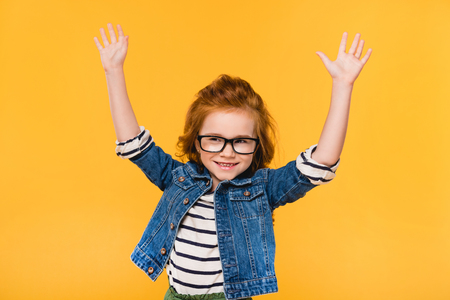 Foto de portrait of cute little kid in eyeglasses with outstretched arms isolated on yellow - Imagen libre de derechos