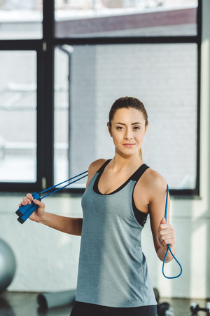 Photo pour portrait of sportswoman with jumping rope looking at camera in gym - image libre de droit
