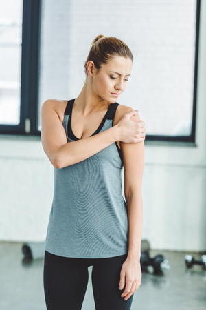 Photo pour portrait of young sportswoman warming up before workout in gym - image libre de droit