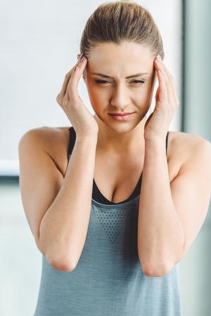 Photo pour portrait of young woman in sportswear having headache - image libre de droit