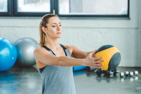 Photo pour portrait of sportswoman doing exercises with ball in gym - image libre de droit
