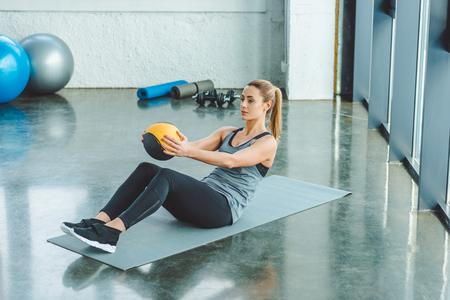 Photo pour sportswoman doing exercises with ball in gym - image libre de droit