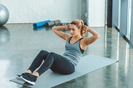 Photo pour young sportswoman doing abs exercises on mat in gym - image libre de droit