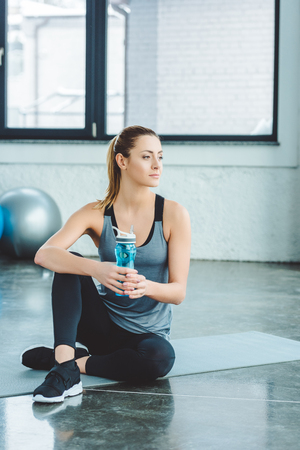 Photo pour sportswoman with water bottle resting on mat after workout in gym - image libre de droit