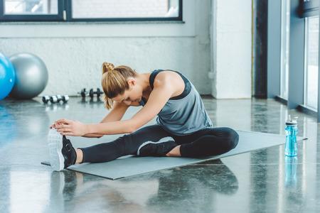 Photo pour sportswoman stretching on mat after workout in gym - image libre de droit
