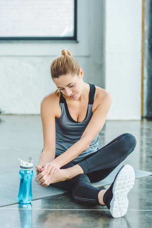 Photo pour sportswoman with injured foot resting on mat in gym - image libre de droit