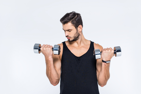 Photo for handsome young man working out with dumbbells isolated on white - Royalty Free Image