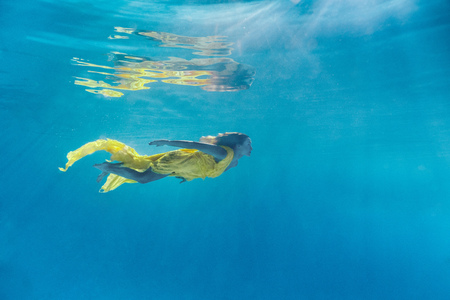 Photo pour underwater picture of beautiful young woman in dress swimming in swimming pool - image libre de droit