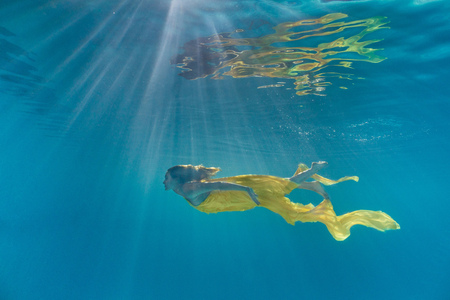 Photo pour underwater picture of attractive young woman in dress swimming in swimming pool - image libre de droit