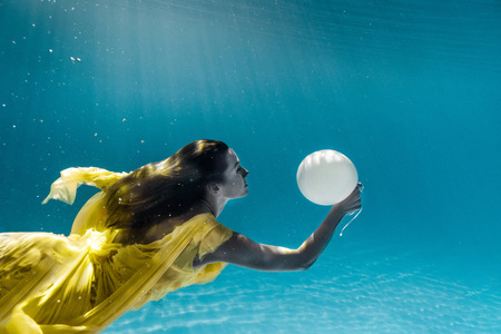 Photo pour underwater picture of beautiful young woman in dress with balloon swimming in swimming pool - image libre de droit