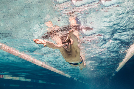Photo pour underwater picture of young swimmer in cap and goggles training in swimming pool - image libre de droit