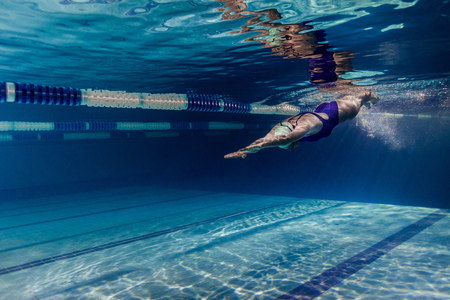 Photo pour underwater picture of female swimmer in swimming suit and goggles training in swimming pool - image libre de droit
