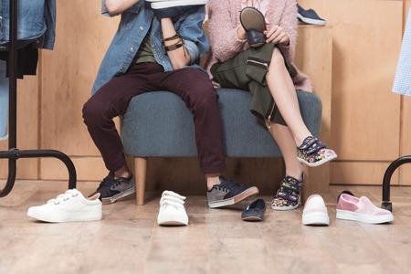 Foto de cropped image of kids sitting on sofa surrounded by scattered shoes on floor - Imagen libre de derechos