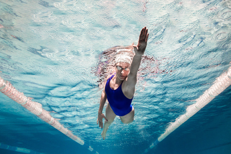 Foto de underwater picture of female swimmer in swimming suit and goggles training in swimming pool - Imagen libre de derechos