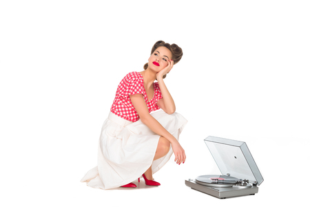 Photo pour pensive woman in pin up style clothing listening to phonograph isolated on white - image libre de droit