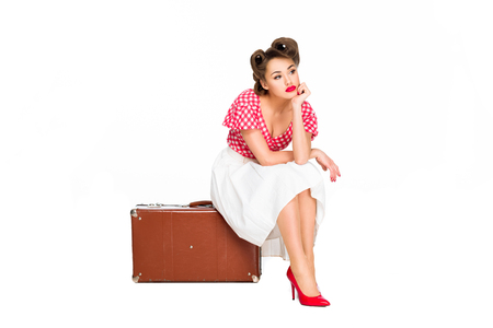 Photo pour bored beautiful woman in retro clothing sitting on suitcase isolated on white - image libre de droit