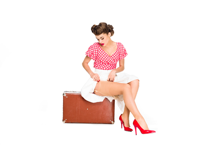 Photo for beautiful young woman in retro clothing sitting on suitcase isolated on white - Royalty Free Image