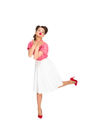 Photo pour beautiful young woman in retro style clothing blowing kiss isolated on white - image libre de droit