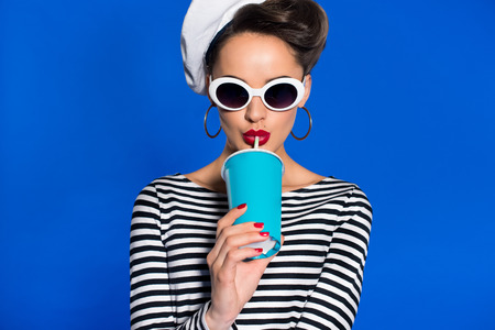 Photo pour portrait of stylish young woman with beverage in paper cup isolated on blue - image libre de droit