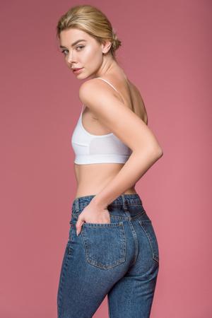 Foto de attractive blonde woman posing in jeans and white bra, isolated on pink - Imagen libre de derechos
