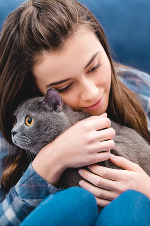 Foto de close-up view of girl hugging adorable british shorthair cat at home - Imagen libre de derechos