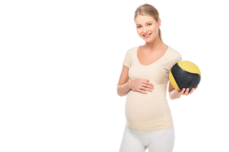 Foto de happy pregnant blonde woman holding ball in left hand isolated on white - Imagen libre de derechos