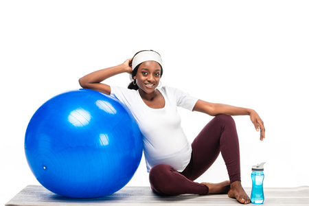 Photo pour african american woman sitting on floor with fitness ball isolated on white - image libre de droit