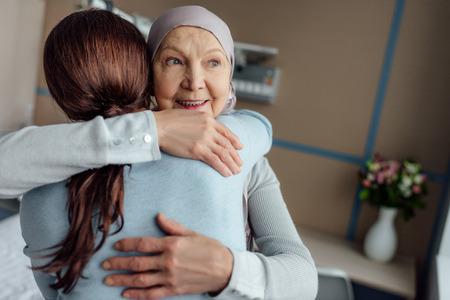 Foto de smiling senior woman in kerchief hugging daughter in hospital - Imagen libre de derechos