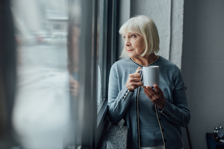 Photo for pensive senior woman holding cup of coffee and looking through window at home - Royalty Free Image
