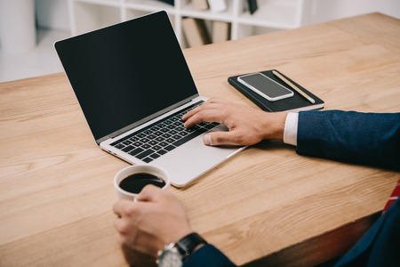 Photo for cropped view of businessman holding cup of coffee while typing on laptop at workplace - Royalty Free Image