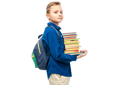 Foto de cute boy holding stack of books and looking at camera isolated on white - Imagen libre de derechos