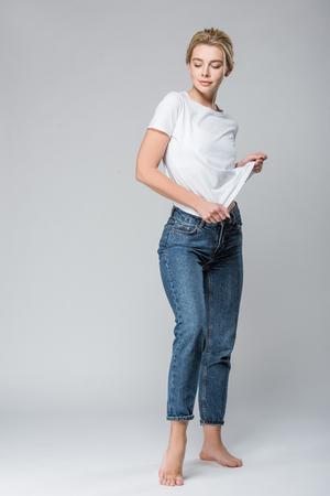 Foto de beautiful smiling woman in jeans undressing isolated on grey - Imagen libre de derechos