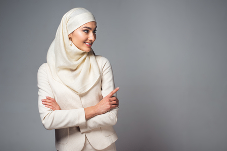 Photo for smiling young muslim woman standing with crossed arms and looking away isolated on grey - Royalty Free Image