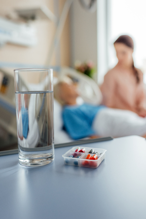 Foto de selective focus of water glass and medicine with patient and visitor on background - Imagen libre de derechos