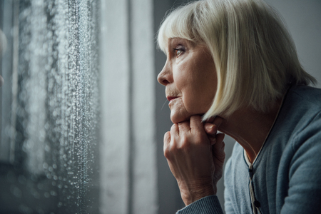Photo for senior woman with grey hair propping chin with hand and looking through window with raindrops at home - Royalty Free Image