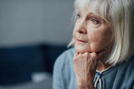 Foto de portrait of thoughtful senior woman propping chin with hand at home - Imagen libre de derechos