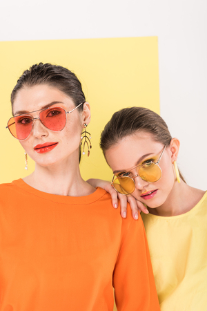 Photo pour beautiful stylish girls in sunglasses looking at camera and posing with limelight on background - image libre de droit