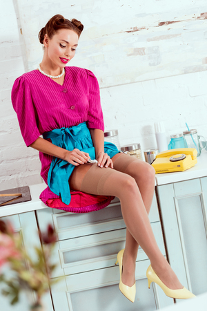 Photo for Beautiful pin up girl in crimson dress sitting on kitchen table - Royalty Free Image