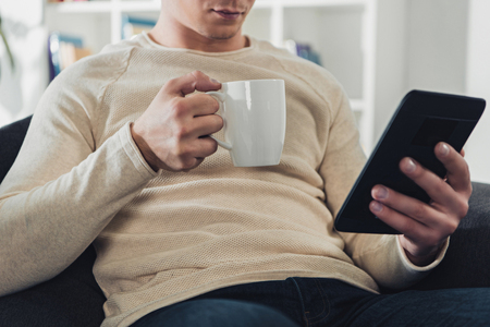 Foto de cropped view of man holding ebook and cup of coffee at home - Imagen libre de derechos