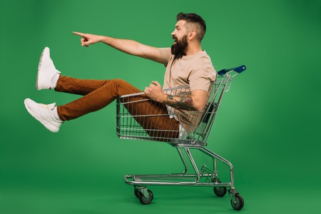 Foto de excited bearded man showing something while sitting in shopping cart isolated on green - Imagen libre de derechos