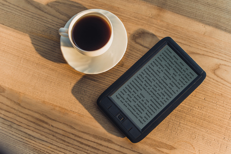 Foto de black e-book lying near cup with drink - Imagen libre de derechos