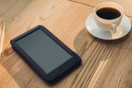 Foto de ebook with blank screen lying near cup with coffee - Imagen libre de derechos
