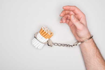 Foto de Partial view of man in handcuffs posing with cigarettes isolated on grey, nicotine addiction concept - Imagen libre de derechos