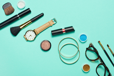 Photo pour Top view of mascara, watch, lipstick, bracelets, eyeshadow, blush, glasses and cosmetic brushes on turquoise background - image libre de droit