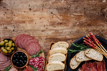 Photo pour top view of cutting boards with olives, breadsticks, prosciutto, salami, bread and herbs on wooden vintage table - image libre de droit