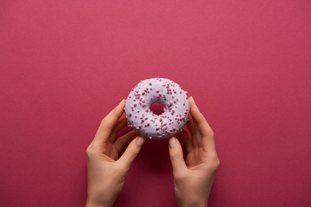 Photo for cropped view of woman holding sweet donut on ruby background - Royalty Free Image