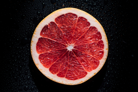 Photo for slice of grapefruit on black background with water drops - Royalty Free Image