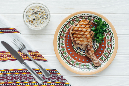 Foto de top view of rib eye meat steak on plate with parsley, sauce, embroidered towel and cutlery on white wooden background - Imagen libre de derechos
