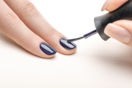 Foto de female manicurist applying navy blue nail polish on fingernail of woman on white background - Imagen libre de derechos